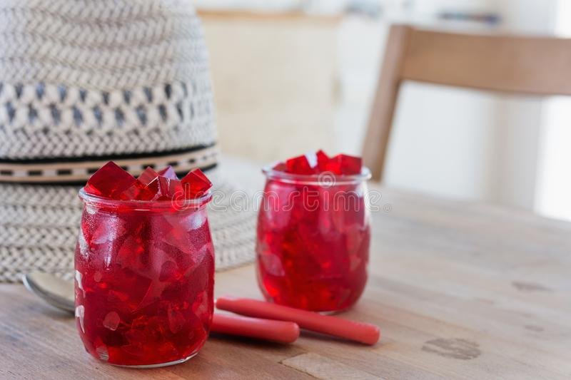 Red jelly, cut into dice, inside two glasses of glass royalty free stock photography
