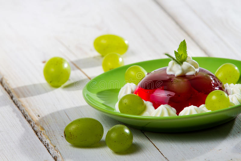 Red jelly and grapes served on a plate royalty free stock photography