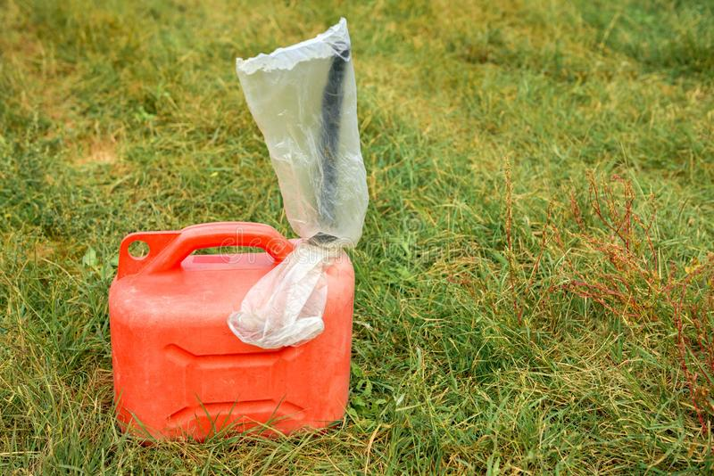 Red jerrycan on green grass. Outdoors closeup photo royalty free stock image