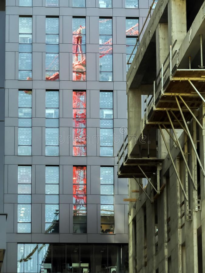 Red jib crane reflection. Red jib crane reflecting in highrise building glass facade stock image