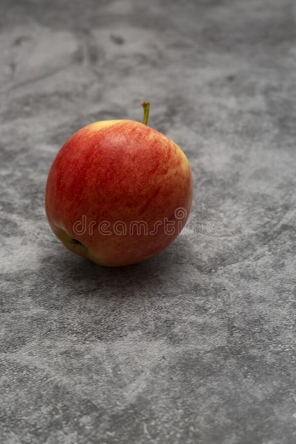 Red juicy apple lies on a gray stone background. Fruit with yellow. Stripes stock photo