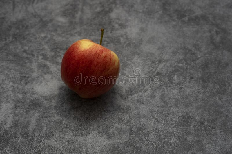 Red juicy apple lies on a gray stone background. Fruit with yellow. Stripes royalty free stock photo