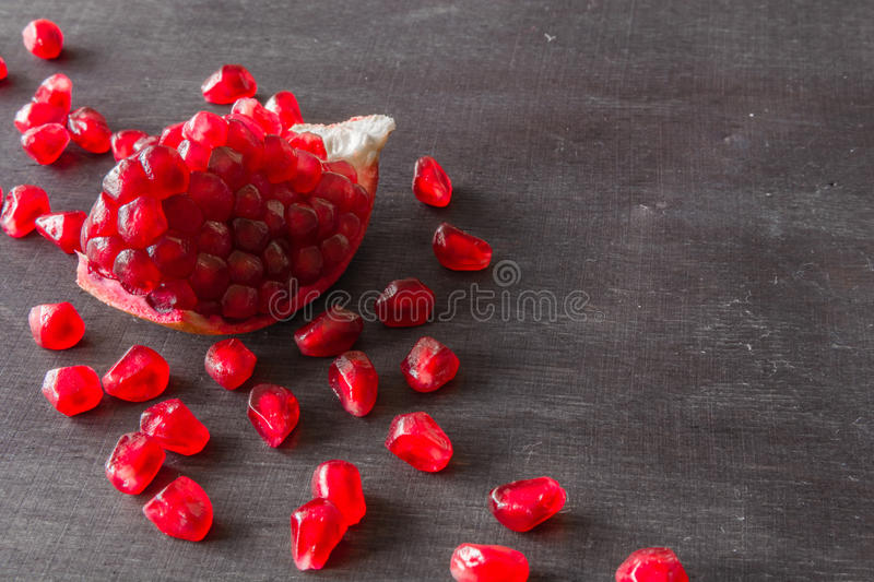 Download Red Juicy Ripe Pomegranate Grains On Dark Wooden Background. Stock Photo - Image: 83720313