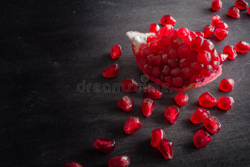 Download Red Juicy Ripe Pomegranate Grains On Dark Wooden Background. Stock Photo - Image: 83720408