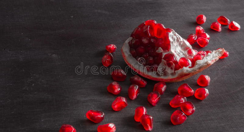 Download Red Juicy Ripe Pomegranate Grains On Dark Wooden Background. Stock Photo - Image: 83720520