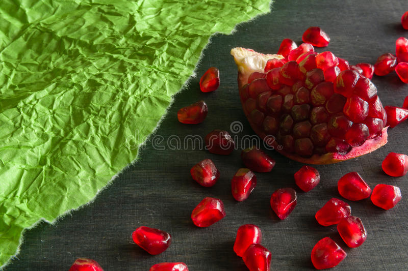 Download Red Juicy Ripe Pomegranate Grains On Green Paper Background. Stock Photo - Image: 83720918