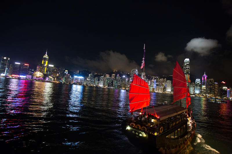 Red Junk in Hong Kong Strait. Red junk sailing on Hong Kong Strait, overlooking the island`s skyline at night stock images