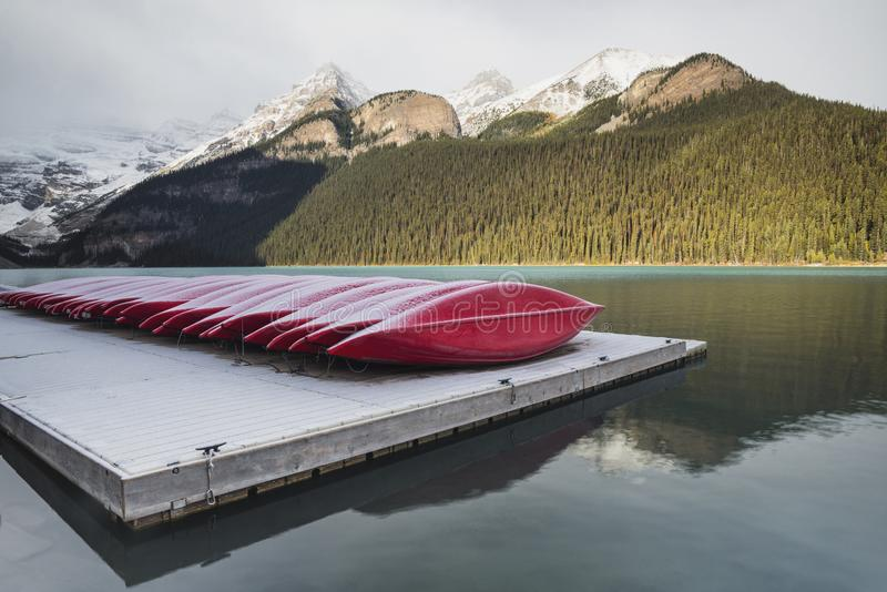 Red kayaks, Lake Louise, Banff National Park, Alberta, Canada. Red canoes and kayaks on a dock on Lake Louise with snow covered mountains, Banff National Park stock photo