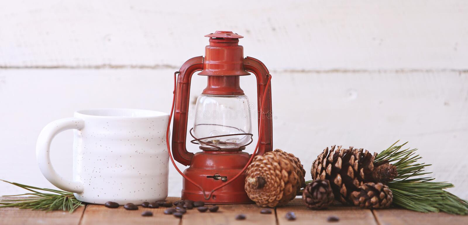 Red Kerosene Lantern Beside White Ceramic Mug on Brown Wooden Table royalty free stock photo
