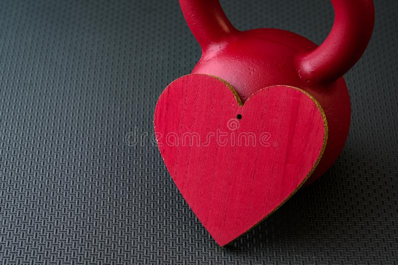 Red kettlebell on a black gym floor with large red heart. To celebrate Valentine's Day fitness royalty free stock image