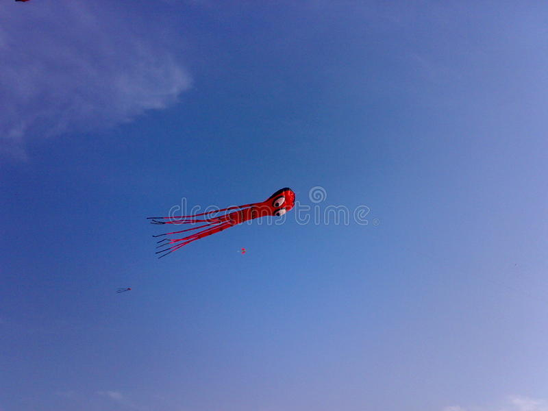 Red Kite in Blue Sky. Red crafted kite flying in Blue sky. Click from a kitefestival in kappad Kerala India stock photos
