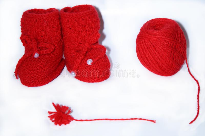 Red knitted baby booties, a red ball of wool yarn for knitting and a red pompon of yarn on a white background stock photo