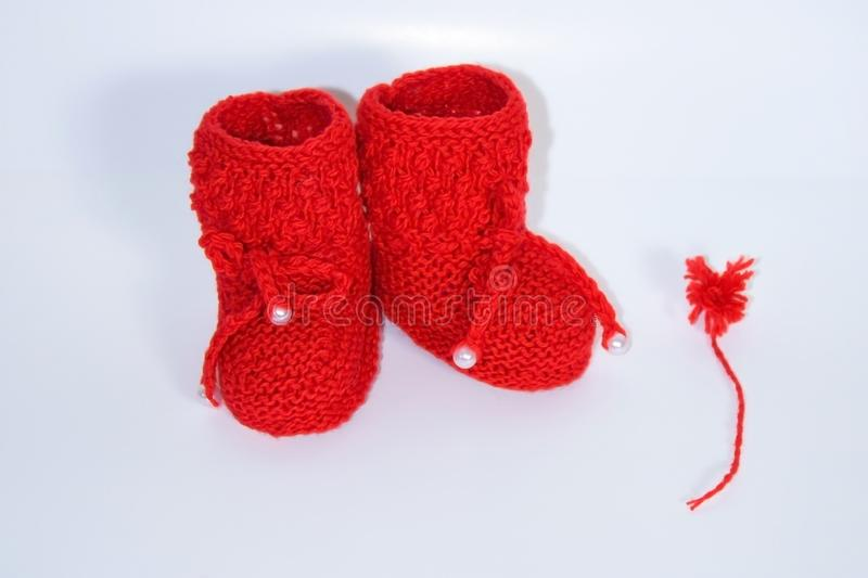 Red knitted baby booties and a red pompon of yarn on a white background royalty free stock photo