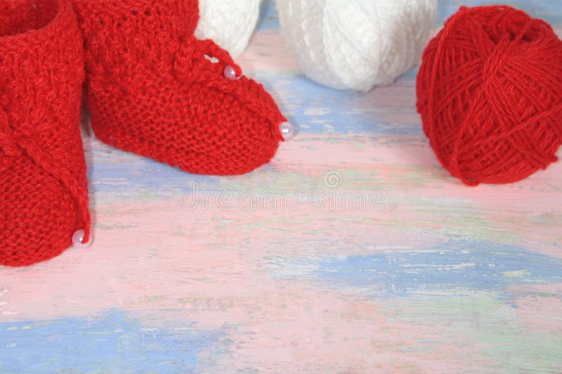 Red knitted baby booties, a red and white balls of wool yarn for knitting on a pink - blue background stock image
