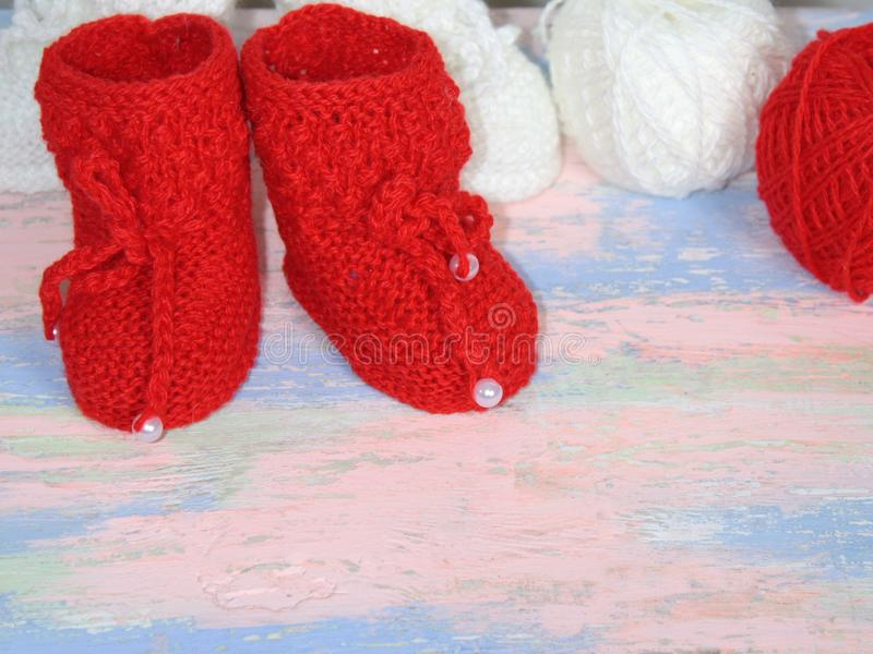 Red knitted baby booties, a red and white balls of wool yarn for knitting on a pink - blue background royalty free stock image
