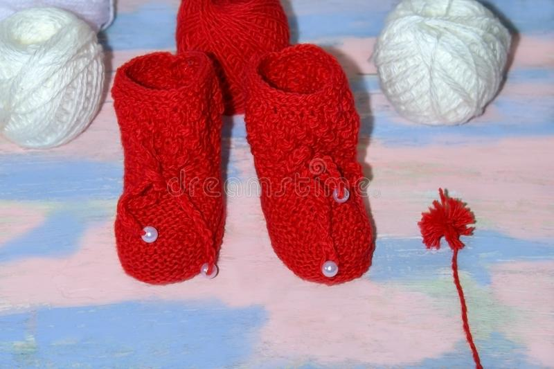 Red knitted baby booties, a red and white balls of wool yarn for knitting and a red pompon of yarn on a pink - blue background royalty free stock photography