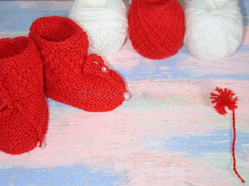 Red knitted baby booties, a red and white balls of wool yarn for knitting and a red pompon of yarn on a pink - blue background royalty free stock images