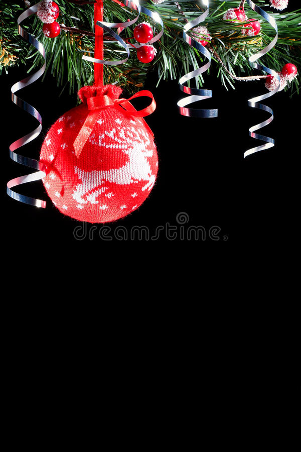 Red knitted Christmas ball. Black background. Decorative knitted red ball on a black background. New Year composition royalty free stock images