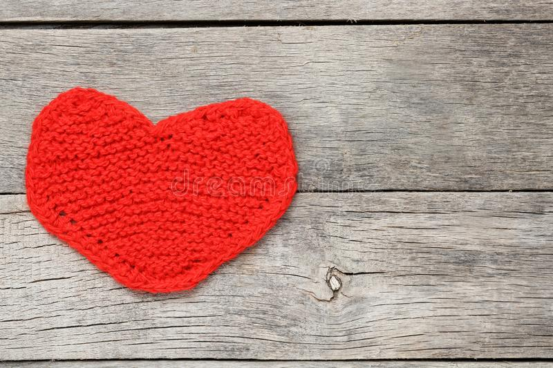 Red knitted heart on a gray wooden background, symbolizing love. Valentine`s Day. Background, cool plan stock photography