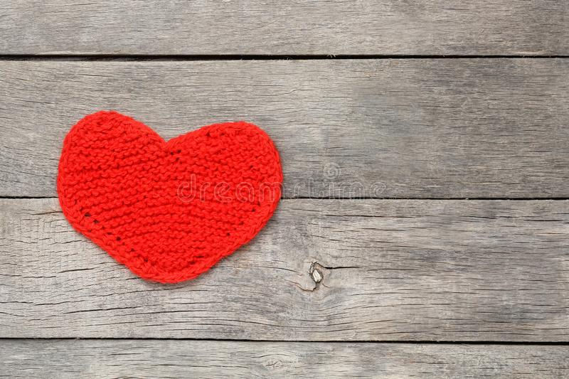 Red knitted heart on a gray wooden background, symbolizing love. Valentine`s Day. Background, cool plan stock image