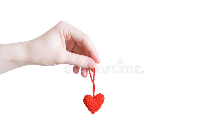 Red knitted heart in the hand of  caucasian girl close-up. White isolate stock photos