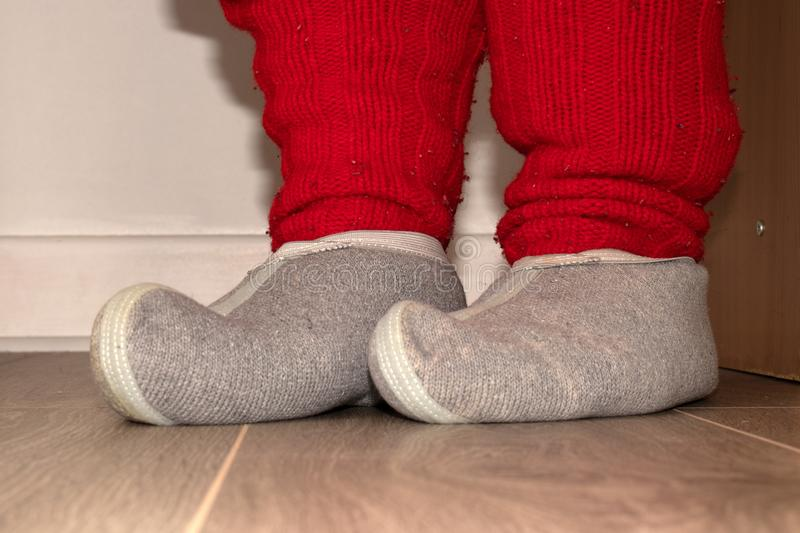 Red knitted socks and woolen slippers on the feet. Red knitted socks of rough wool and woolen slippers on the feet of a person royalty free stock photography