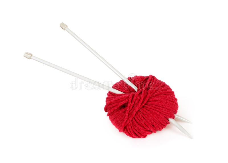 Red knitting wool and needles over white
