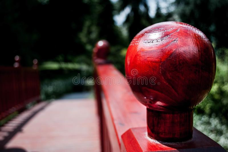 Red knob on a handrail. Closeup of a red knob located on the handrail along a bridge stock image