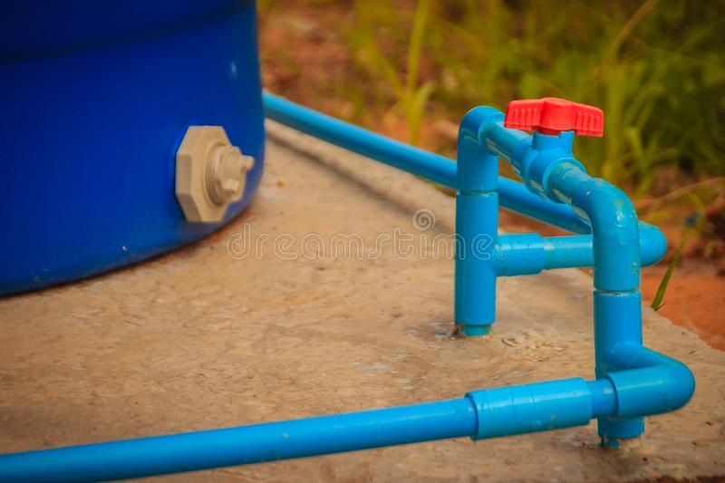 Red knob of PVC ball valve on the PVC pipe line in plumbing system for control the water to storage tank. stock image