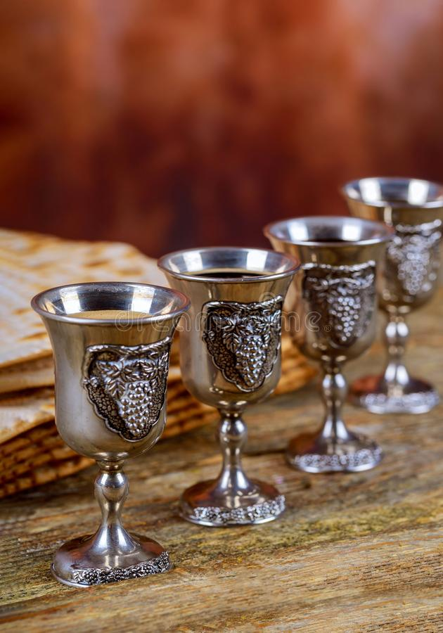 Red kosher wine four of matzah or matza Passover Haggadah. Red kosher four glasses wine with a of matzah a Passover Haggadah celebration jewish holidays seder stock photo