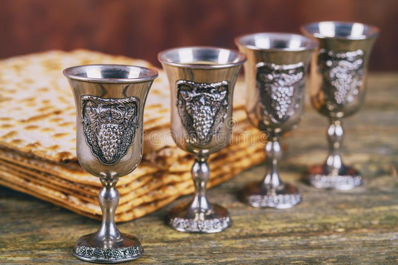 Red kosher wine four of matzah or matza Passover Haggadah on a vintage wood background. Red kosher four glasses wine with a of matzah a Passover Haggadah on a royalty free stock photo