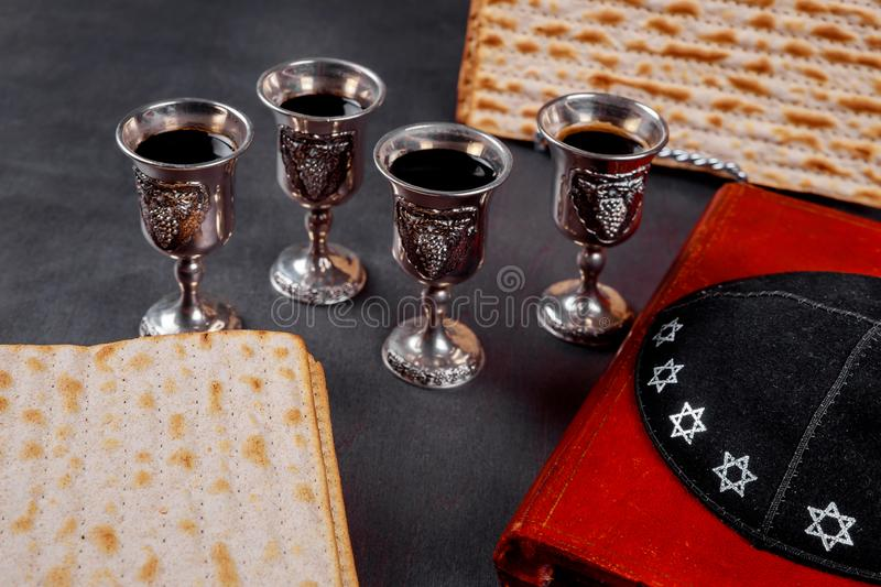 Red kosher wine four of matzah or matza Passover Haggadah on a vintage wood background. Red kosher four glasses wine with a of matzah a Passover Haggadah on a royalty free stock image