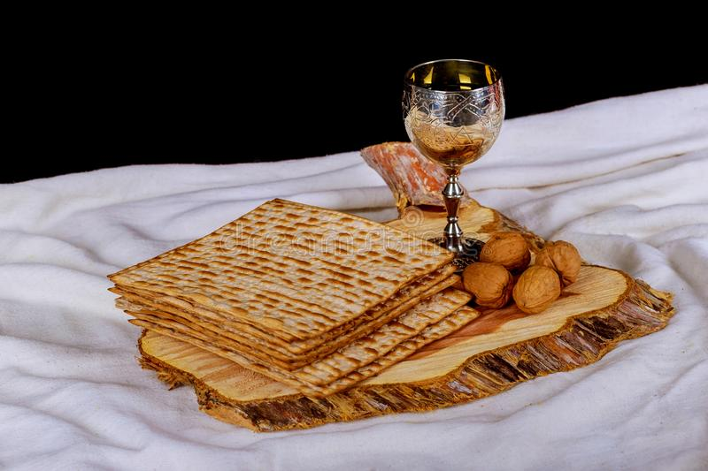 Red kosher wine with a white plate of matzah or matza and a Passover Haggadah on a vintage wood background. Perfect for your Passover design mock up royalty free stock photography