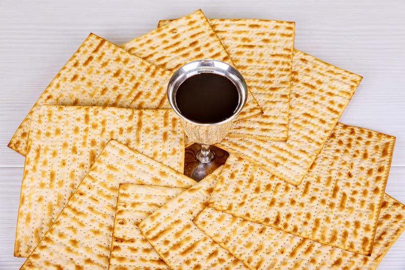 Red kosher wine with a white plate of matzah or matza and a Passover Haggadah on a vintage wood background presented as a Passover. Seder meal with copy space stock image