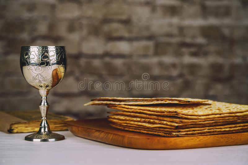 Red kosher wine with a white plate of matzah or matza and a Passover Haggadah on a vintage wood background presented as a Passover. Seder meal with copy space royalty free stock image