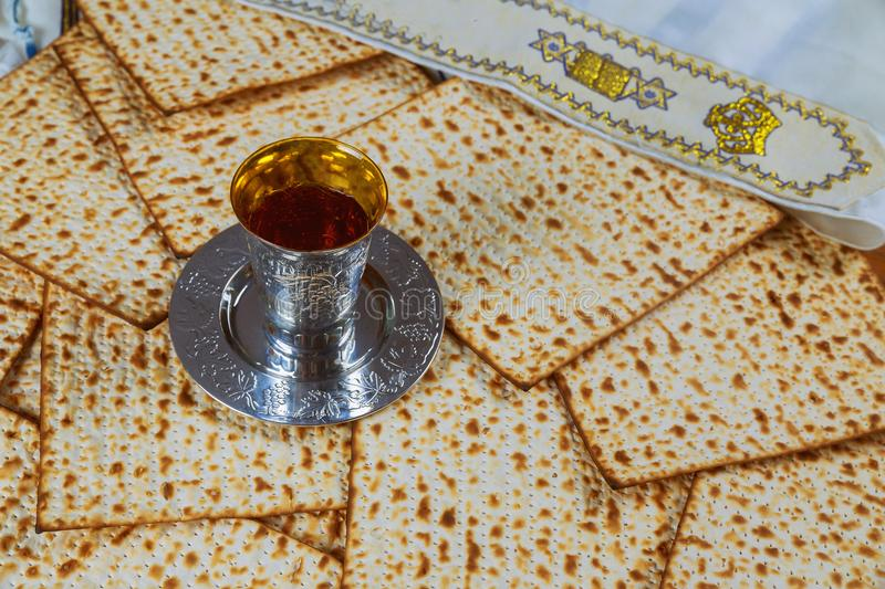 Red kosher wine with a white plate of matzah or matza and a Passover Haggadah on a vintage wood background presented as a Passover. Seder meal with copy space stock images