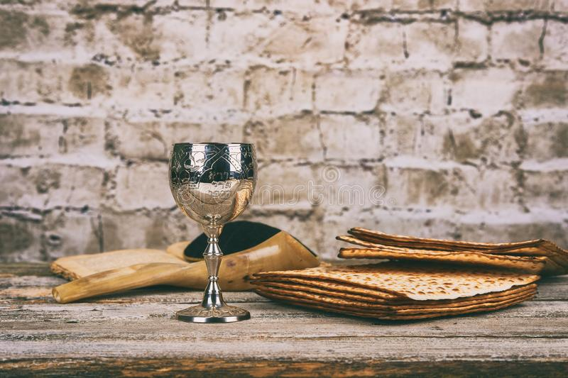 Red kosher wine with a white plate of matzah or matza and a Passover Haggadah on a vintage wood background presented as a Passover. Seder meal with copy space stock photos