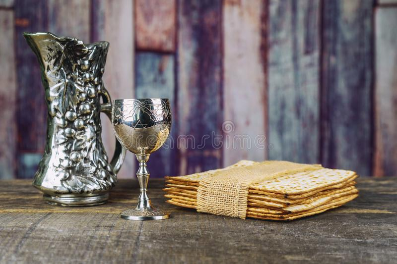 Red kosher wine with a white plate of matzah or matza and a Passover Haggadah. On a vintage wood background stock photos
