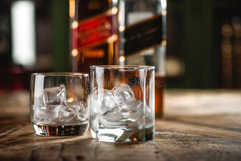 Red label and Black label whiskey bottles and glass with ice cub. Es on wooden table. Johnnie Walker is Scotch blended whiskey and one of famous brands in world stock images
