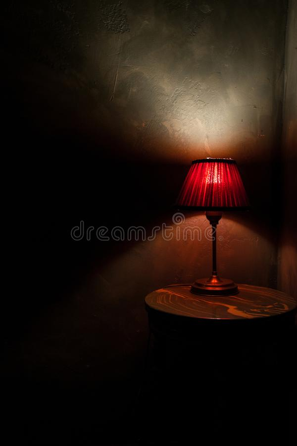 Red lamp on a brown , round table. A red lamp , standing on a brown , wooden table with grey texture wall behind it royalty free stock photo