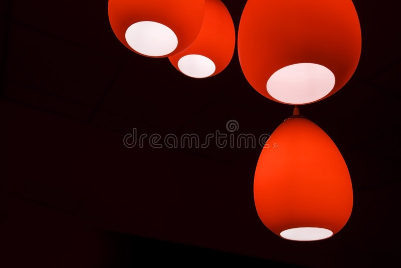 Red lamps. Four red modern lamps in a black room stock photos