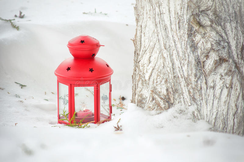 Red lantern with lighted candle in the snow stock photo