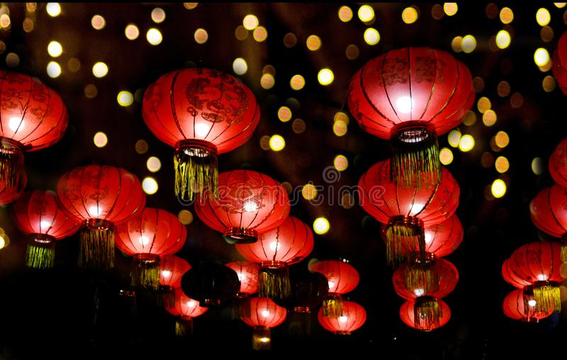 Red lanterns for Chinese New Year at night, against the background of multi-colored bokeh. Decorated with lights at night for stock image