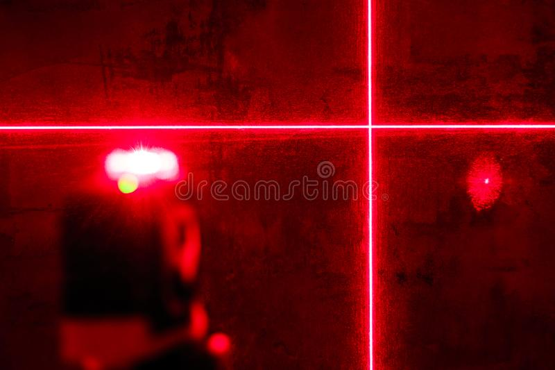 . red laser level. carving in a dark room. shallow depth of field stock image