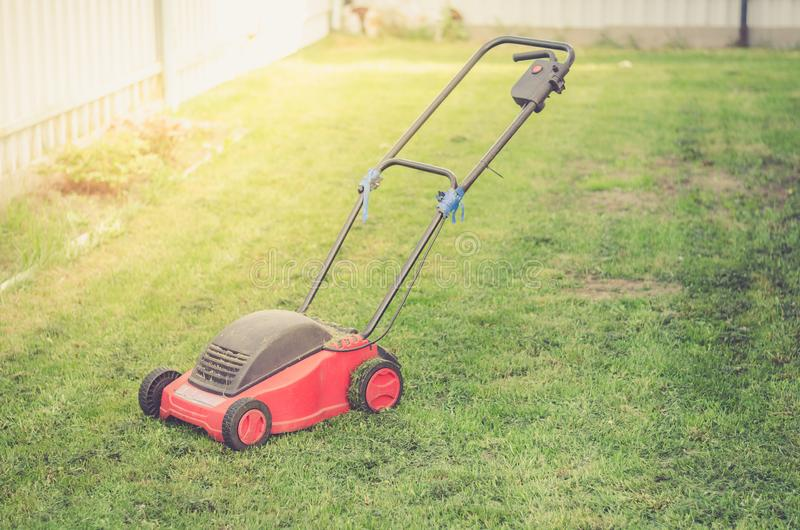 Red Lawn mower cutting green grass/mowing lawn on the grass in the cottage yard royalty free stock photography