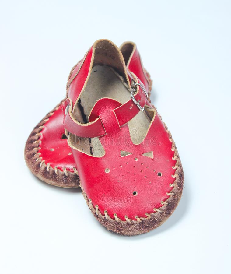 Red leather baby sandals. On a white background royalty free stock images