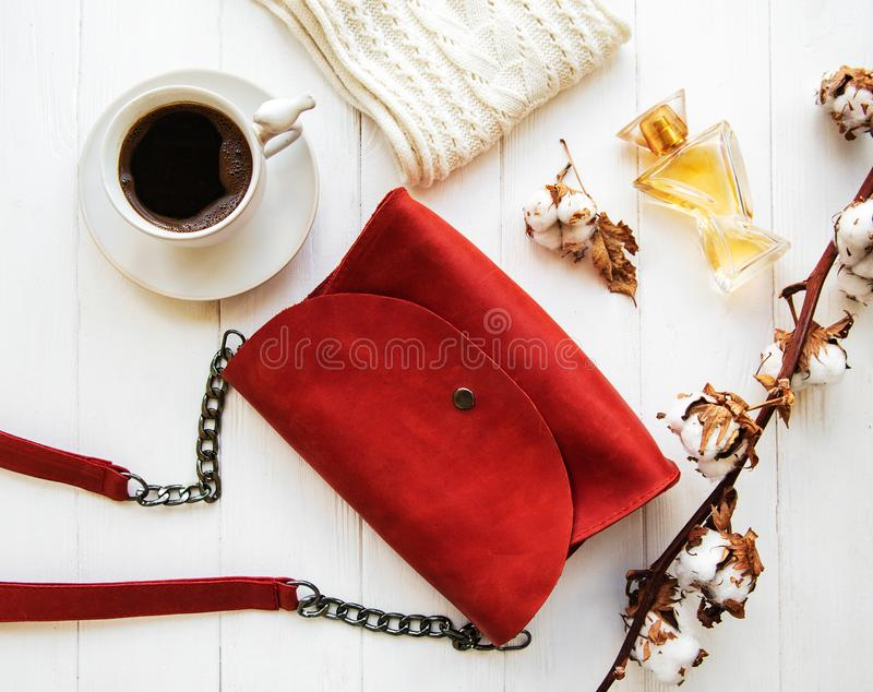 Red leather bag and cotton flowers. On a wooden background stock images
