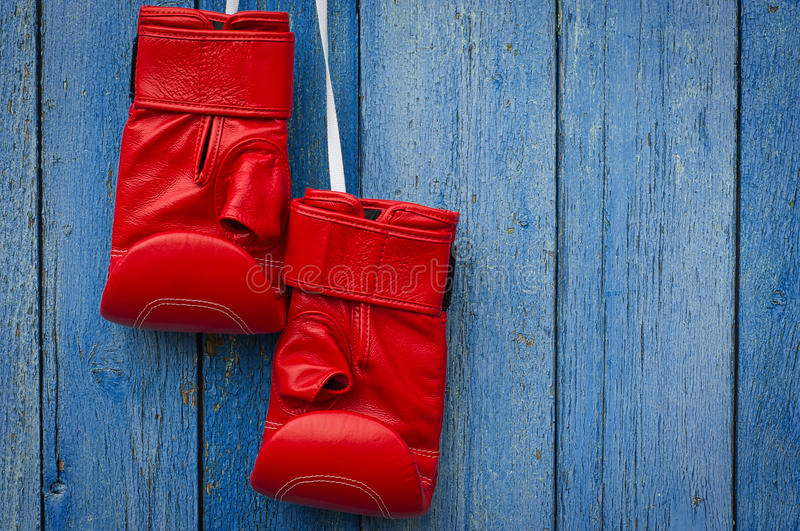 Red leather boxing gloves hanging on a rope. Blue shabby wooden background royalty free stock image