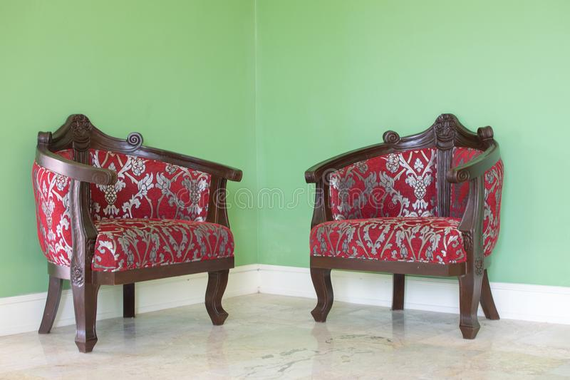 Red leather chairs in the corner with green walls as background. stock photography