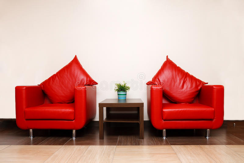 Red leather chairs with pillow. A plant in a pot on a table royalty free stock photos